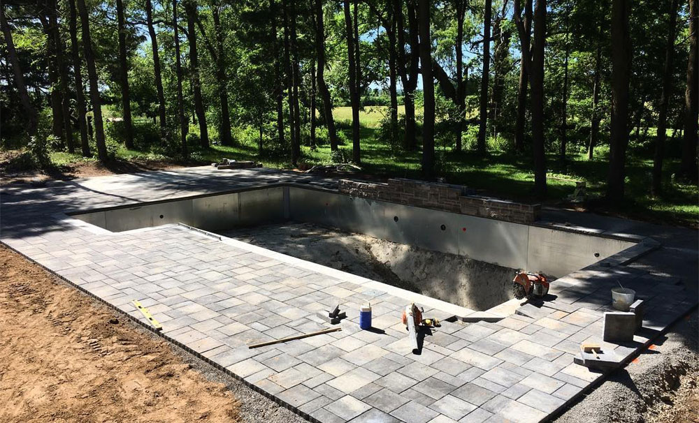Patio being constructed around an in-ground pool