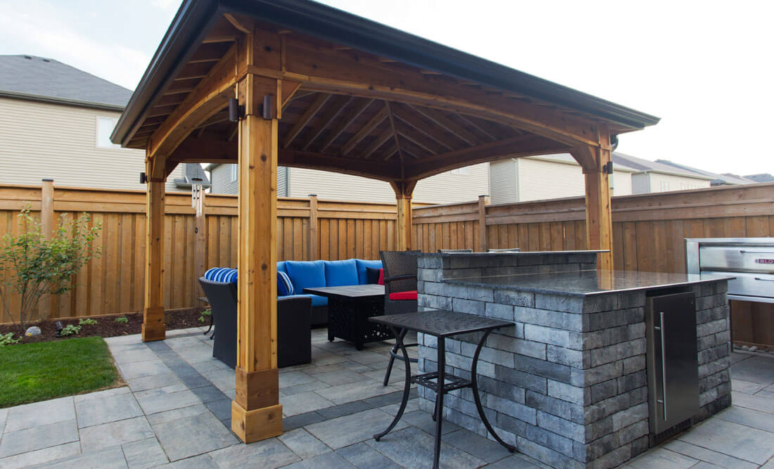 Shade structure with patio bar and partial outdoor kitchen